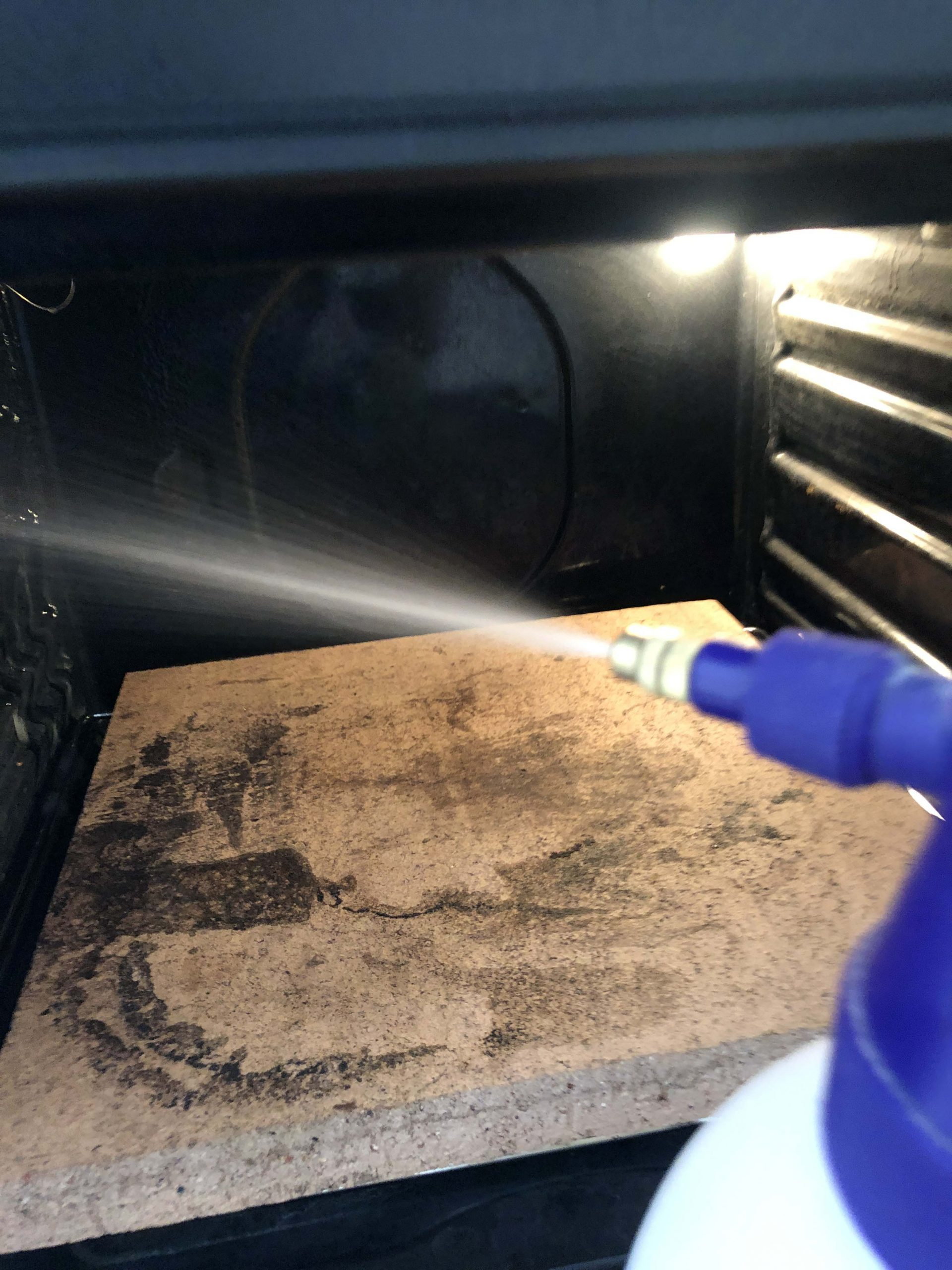 spraying the oven with a water mister